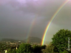 primary and secondary rainbow over town and hill