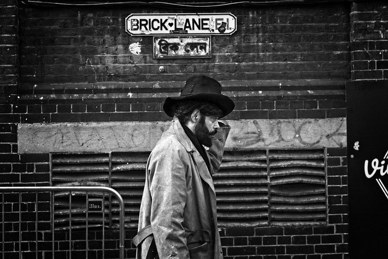 A man walks past a street sign that reads 'Brick Lane, E1'