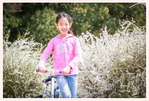 スクーターに乗る女の子 雪柳の花