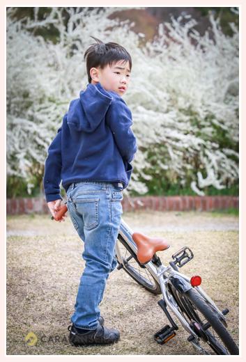 雪柳の前で自転車に乗る男の子