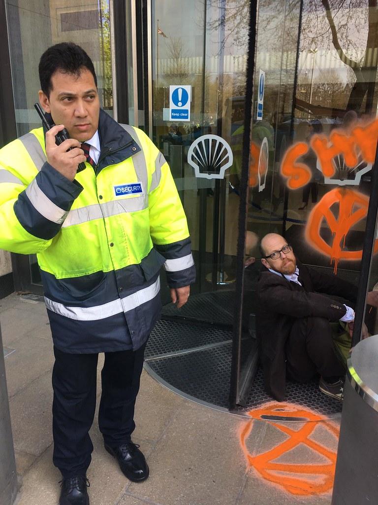 幾名抗議者將自己「黏」在殼牌總部門口的旋轉門,其中包括資深國際環保法專家與律師雅美(Farhana Yamin),她隨後也遭到警方逮捕。圖片來源:Extinction Rebellion