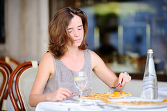 Young woman eating italian pizza in outdoors restaurant