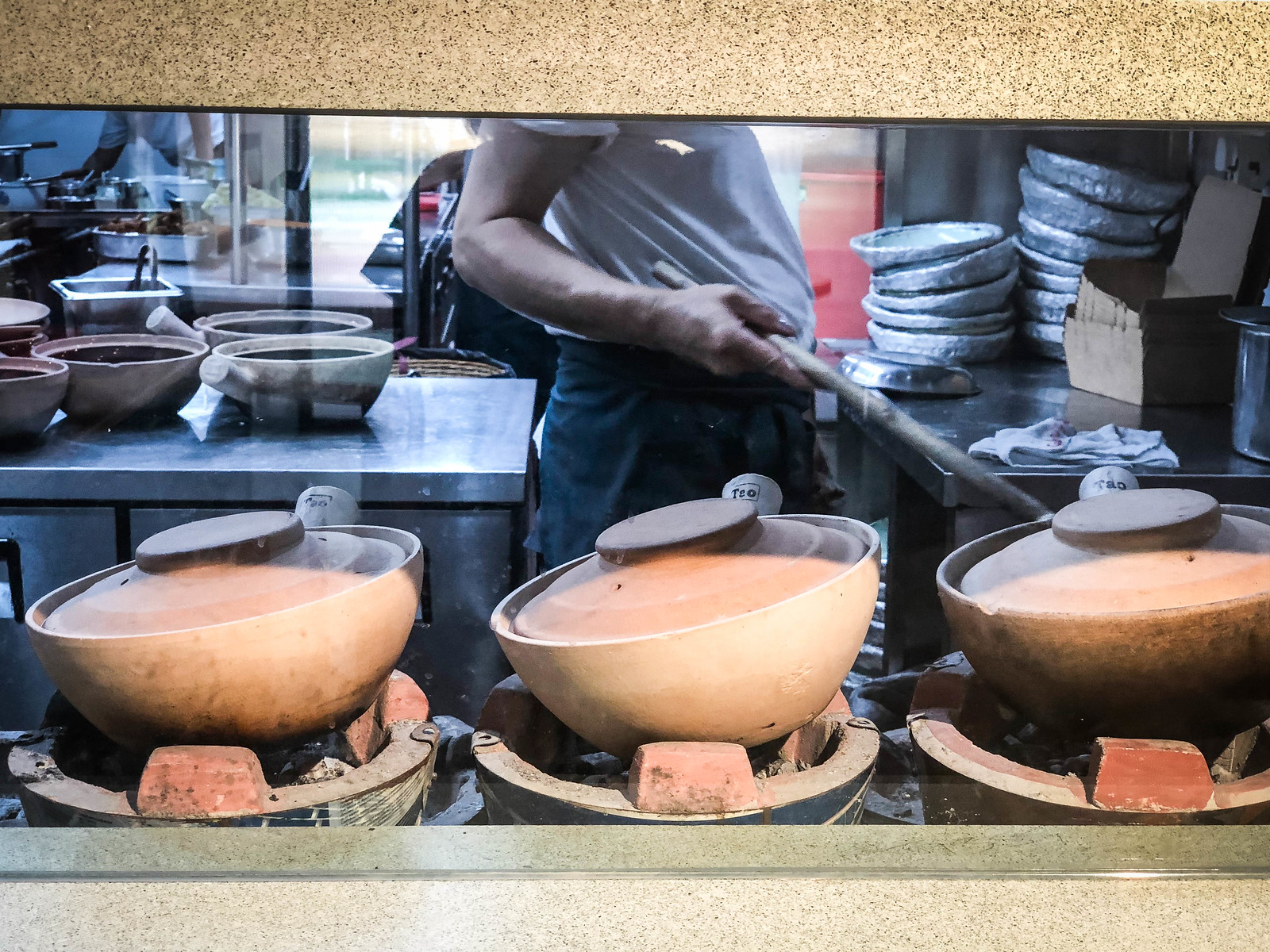 Three claypots cooking on a stove