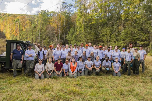 Group photo of MCC members in a wooded area