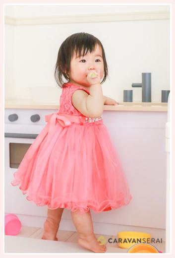 赤いドレスを着て立つ1歳の女の子