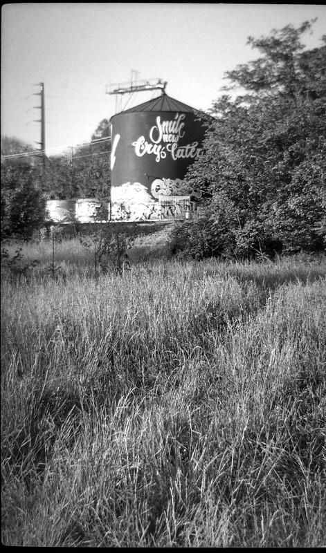 "storage silo, railroad, grass, ""Smile Now Cry Later,""  Asheville, NC, Bencini Koroll 24S, Kodak Tri-X 400, HC-110 developer, 5.2.19"