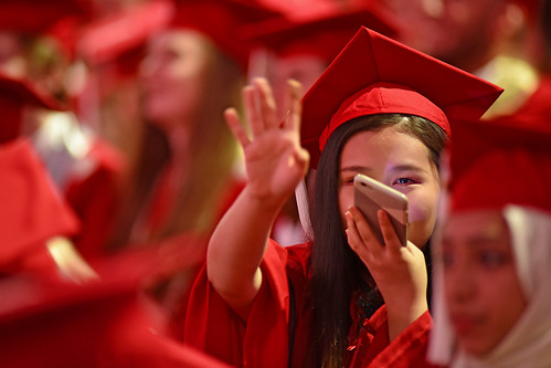 Student waves to family after entering PNC Arena for commencement.