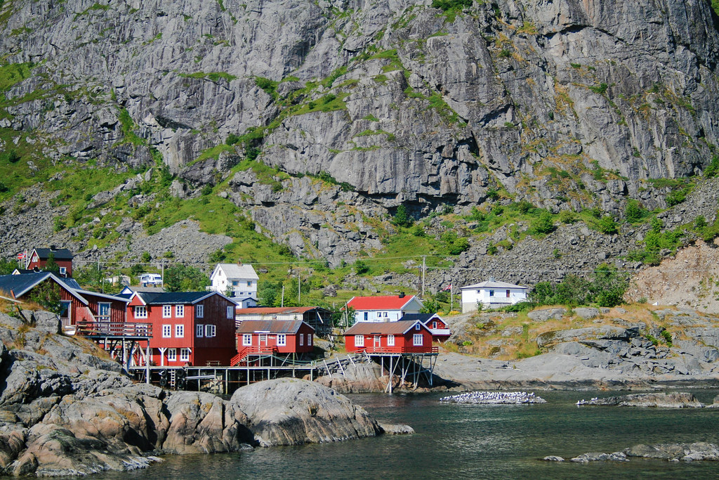 A view of red cabins on the edge of the water, with a mountain behind