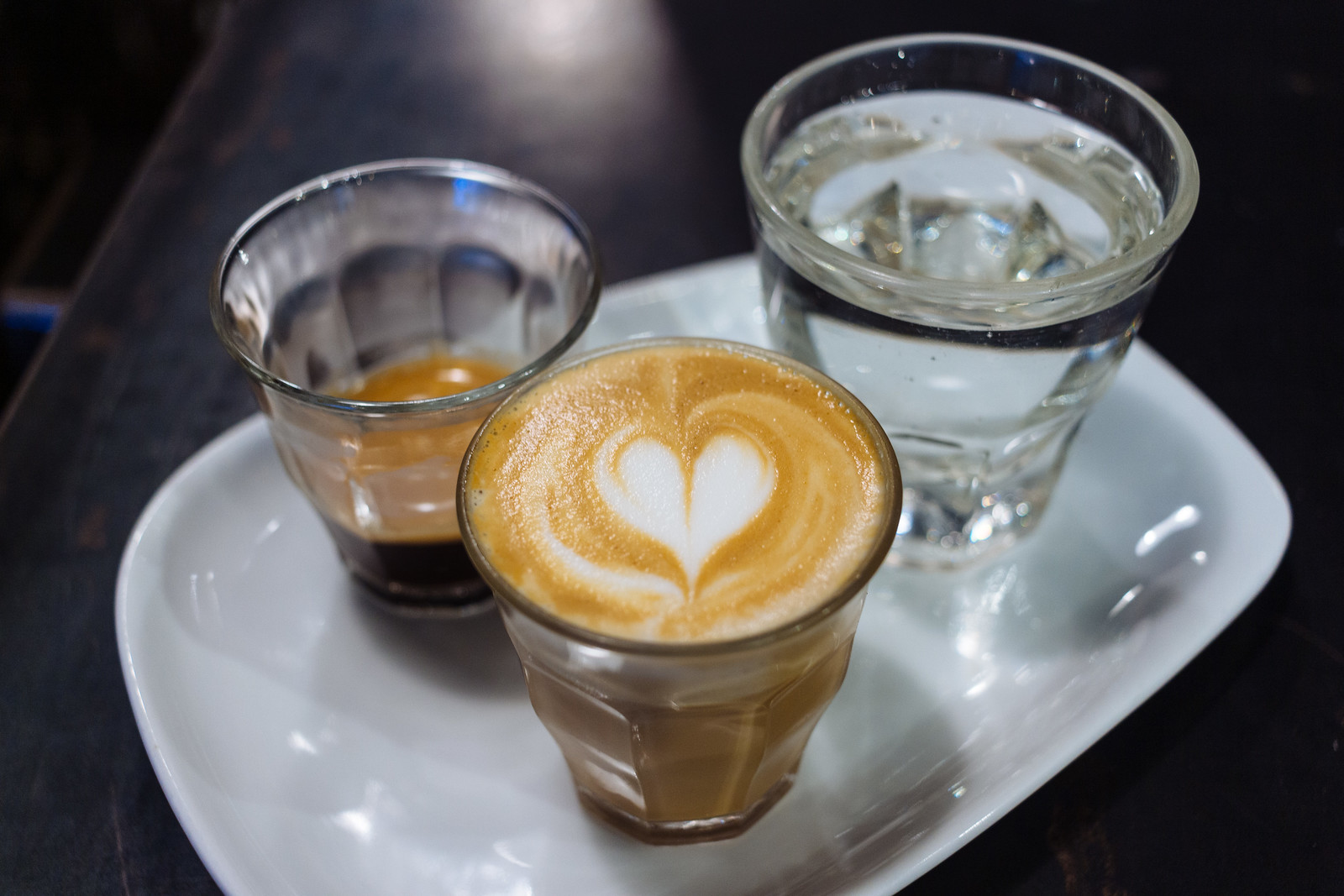 Small glasses of pure espresso, espresso and steamed milk, and sparking water