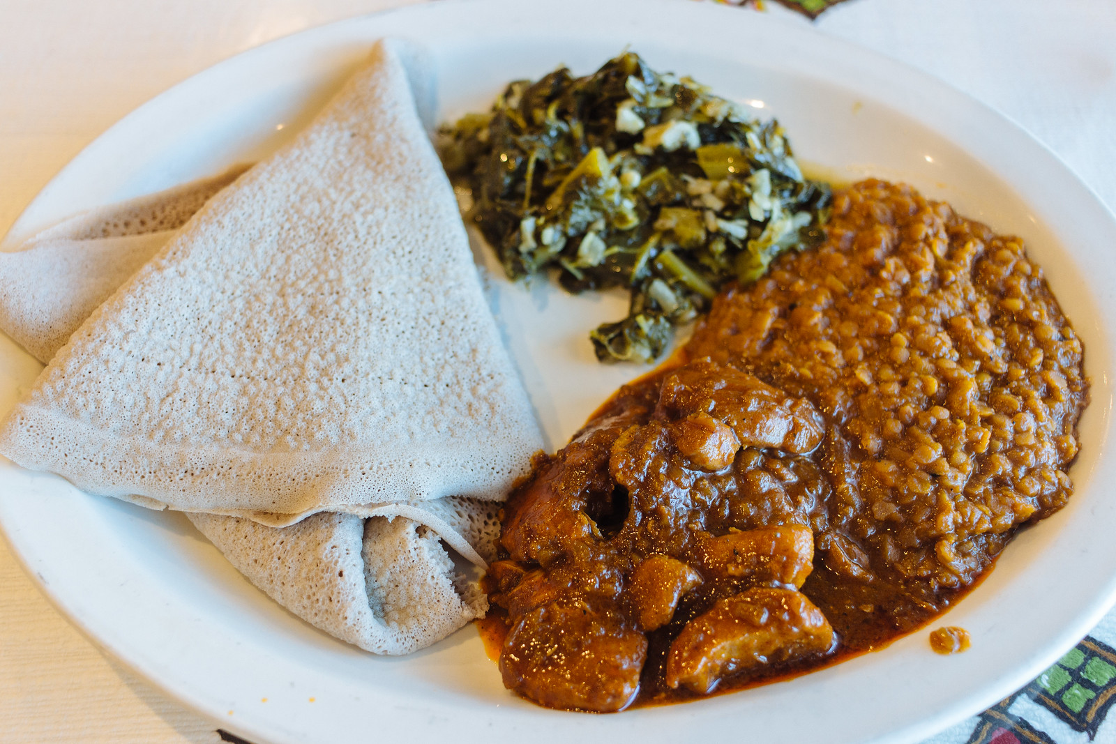 Spiced chicken in a sauce with lentils and greens and folded, spongey bread