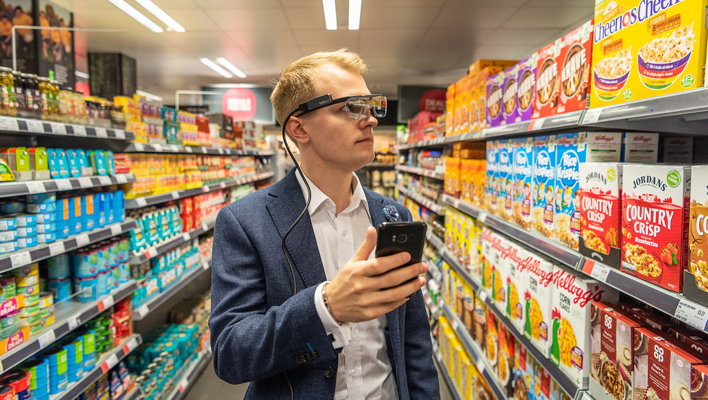 Dr Ahlbom in a supermarket wearing eye-tracker glasses and holding a mobile phone