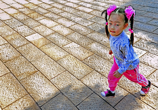 China 2009. Nanchang. Cute little girl with mats and pink flowers in her hairs …