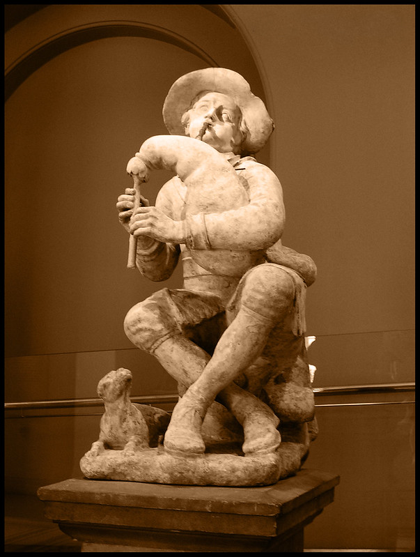 An image of a sculpture, which shows a young boy playing the bagpipes while a dog sits at his feet, looking up at him. Pipers would play for money in days gone by.