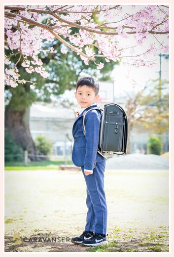 桜の花の下でランドセルを背負って立つ男の子 小学校入学記念