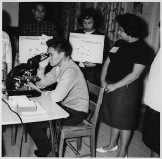 Students in the Community Health Worker Training Program hold up study cards behind a young man looking into a microscope... / Étudiants du Programme de formation des agents de santé communautaire tenant de grandes fiches derrière un jeune homme en t