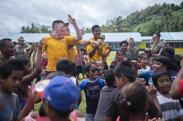 """UDOT, Federated States of Micronesia (April 18, 2019) U.S. Navy Sailors dance with Chuukese children while the Pacific Partnership 2019 """"Black Sands"""" Brass Band perform at a band concert during Pacific Partnership 2019.  Pacific Partnership, now in its 14th iteration, is the largest annual multinational humanitarian assistance and disaster relief preparedness mission conducted in the Indo-Pacific. Each year, the mission team works collectively with host and partner nations to enhance regional interoperability and disaster response capabilities, increase stability and security in the region, and foster new and enduring friendships in the Indo-Pacific. (U.S. Navy photo by Mass Communication Specialist 3rd Class Chanel Turner)"""