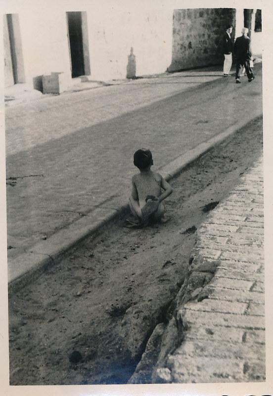 Un niño defecando en la calle junto al puente de san Martín en los años 50. Fotografía de Victoriano de Tena Sardón