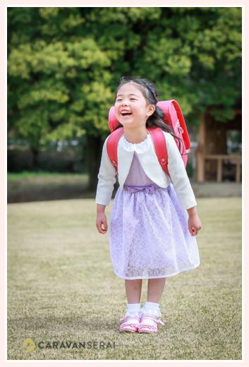 入学式用のワンピースを着てランドセルを背負った女の子 公園にて