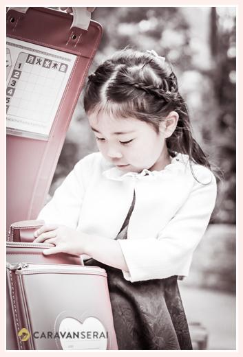 真新しいランドセルを覗き込む新一年生の女の子 モノクロ写真