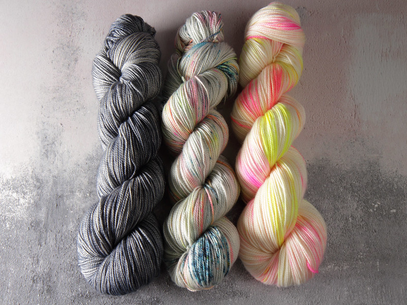 Hand dyed yarn skeins arranged in a fade from grey to neon