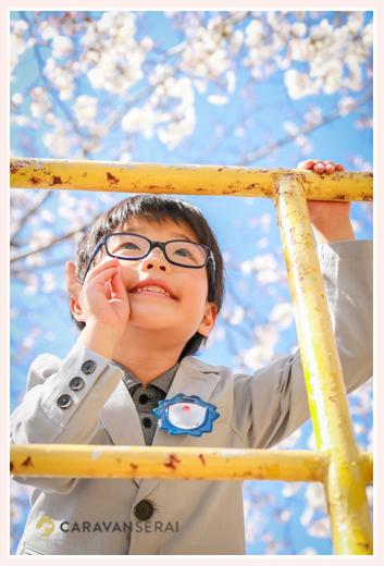 青空と桜をバックに新一年生の男の子