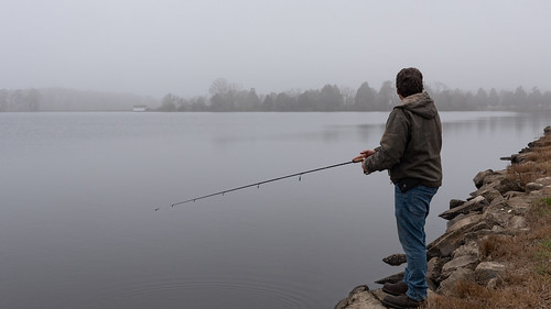 Photo of man fishing along riverside
