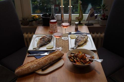 Dorade mit mediteranem Gemüse und Baguette (Tischbild)
