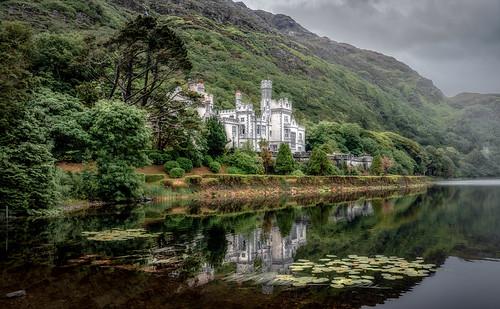 kylemore abbey estate pollacapall lough landscape castle house architecture lake trees mountain cloud rainy plants green gray white romantic