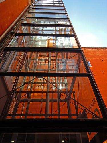Retrofitted glass elevator in an orange building in Copenhagen, Denmark