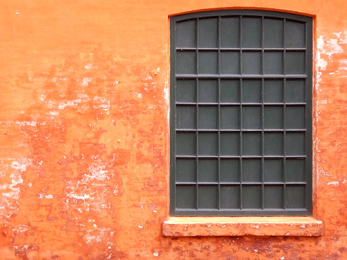 Orange wall with a black gridded window in Christiania, Copenhagen, Denmark