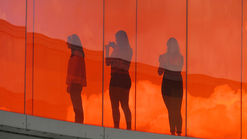 Three women taking photos from the orange section of the Rainbow Walk on the top of the ARoS Museum of Modern Art in Aarhus, Denmark
