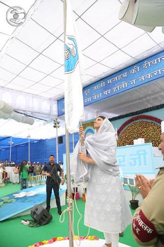 Satguru Mata Ji hoisting the white flag, a symbol of Love, Peace and Unity