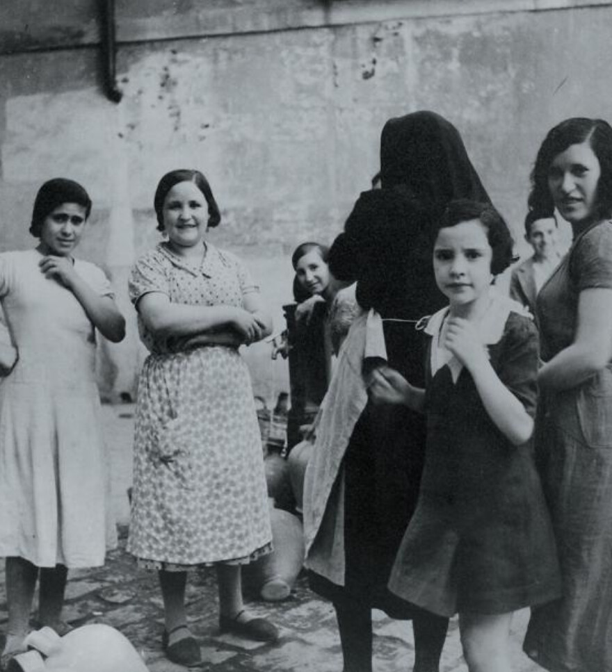 Mujeres y niñas en la fuente de la Plaza de San Nicolás hacia 1934.  Fotografía de Blanc & Demilly