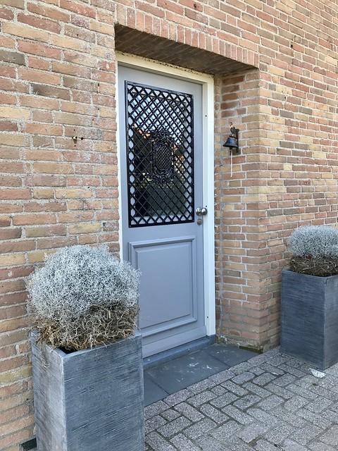 Grijze voordeur landelijk met raster