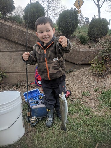 Three-year-old Benjamin Hudak proudly holds up his first fish