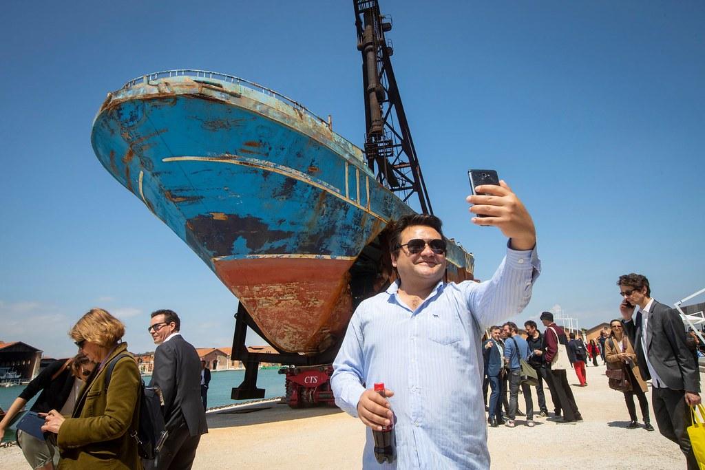 威尼斯雙年展訪客於船難殘骸前自拍。(圖片來源:David Levene/The Guardian)