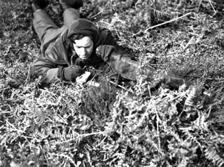Rifleman J.J. Showers of the Queen's Own Rifles of Canada armed with a No4 Mk1 (T) rifle fitted with a Canadian Mk1 Observing Sniper Telescope... / Le carabinier J.J. Showers du régiment d'infanterie The Queen's Own Rifles of Canada armé d'une carabi