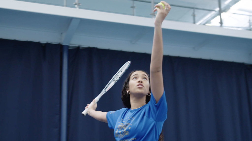A student hitting a ball with a tennis racket.
