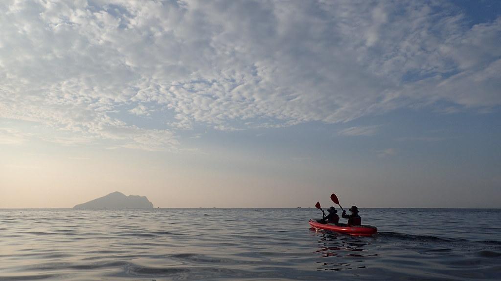 在晨曦下,筆者與眾多舟友一同划向龜山島