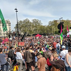 #extinctionrebellion gathering at Marble Arch, discussing their next moves. Mostly people sitting on the ground listening to others speak from a stage. Some music on the fringes but generally quiet and organised. Tents around the water feature on the roun