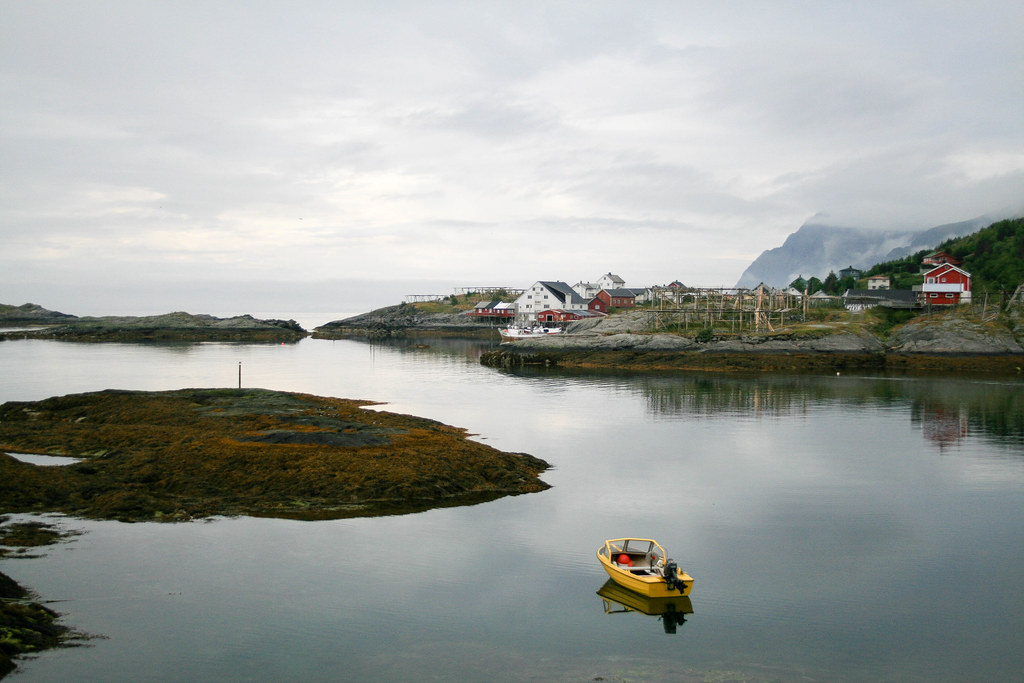 A wild landscape from Lofoten Islands, with a couple of houses in the back and a lonely boat on the water