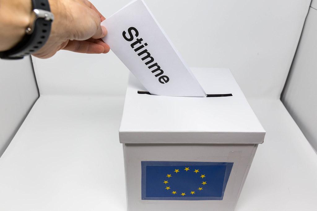 Mann nimmt von seinem Wahlrecht gebrauch und stimmt ab für die Europawahl, indem er seinen Wahlschein in die Urne steckt