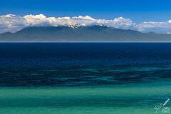 "Mount Olympus is seen from afar (from 35 miles away) on the horizon above Aegean sea. It is the highest mountain in Greece, rising to 9,570 ft, still snow-capped in May, playing hide-and-seek in cloud-laden skies.  The photograph was taken from Kalikrateia in Chalkidikē peninsula.  Jove's (Zeus's) and other gods' mythological residence has long inspired a legion of poets, including Homer:  ""Fly to Olympus, to the feet of Jove, And make thy pray'r to him, if on his heart Thou hast in truth, by word or deed, a claim""  —Homer (Iliad, book I 394-395)  Homer's original text in ancient Greek: 🇬🇷  « ἐλθοῦσ᾿ Οὔλυμπόνδε Δία λίσαι, εἴ ποτε δή τι ἢ ἔπει ὤνησας κραδίην Διὸς ἠὲ καὶ ἔργῳ. »  —Ὁμήρου Ἰλιὰς Α 394-395"