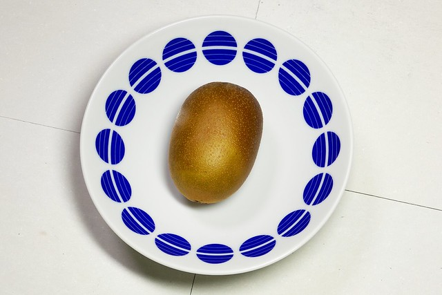 Kiwifruit_(2019_05_19)_2_resized_1 青色の模様が描かれた白色の丸い皿に乗った1個のキウィフルーツを斜め上から撮影した写真。