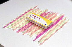 Plastic in the health industry. A stock photo of an array of coloured plastic straws alongside medication.
