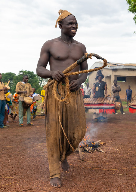 Young Senufo shirtless man dancing the Ngoro with a whip during a ceremony, Savanes district, Ndara, Ivory Coast