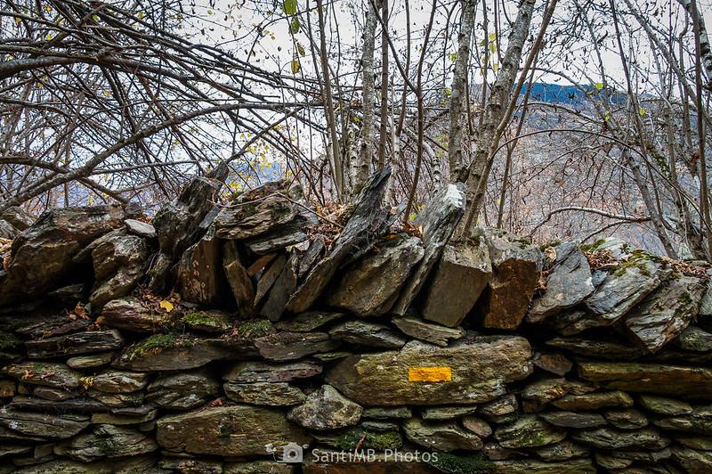 Marca amarilla del Camin de Carlac en un viejo muro de piedra