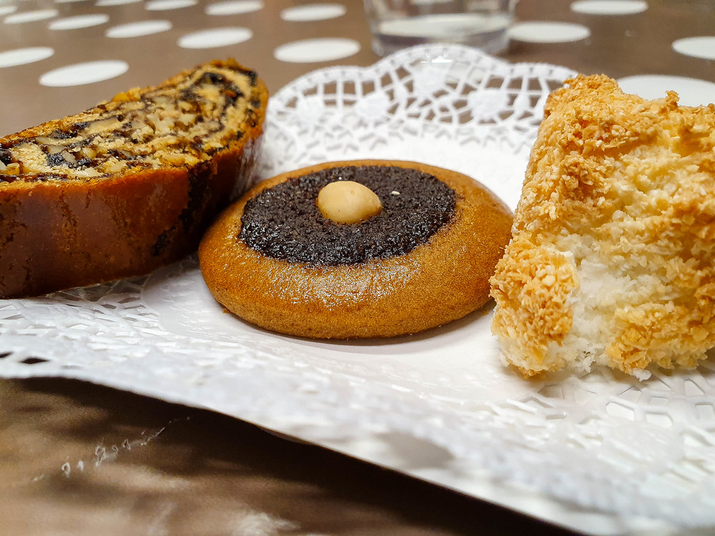 An array of three cookies: plum jam and walnuts roll, gingerbread and poppy seeds cookie, and toasted coconut cake