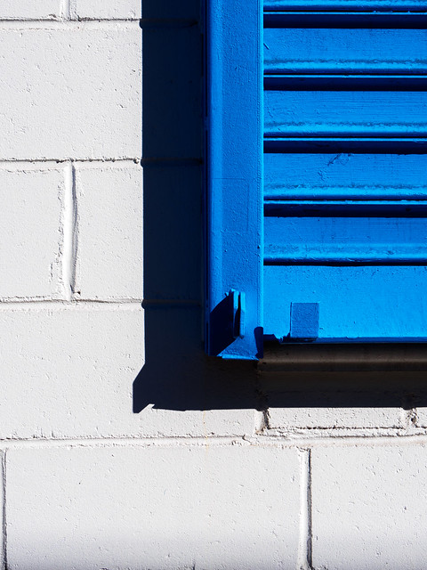 Blue shutter on a white wall
