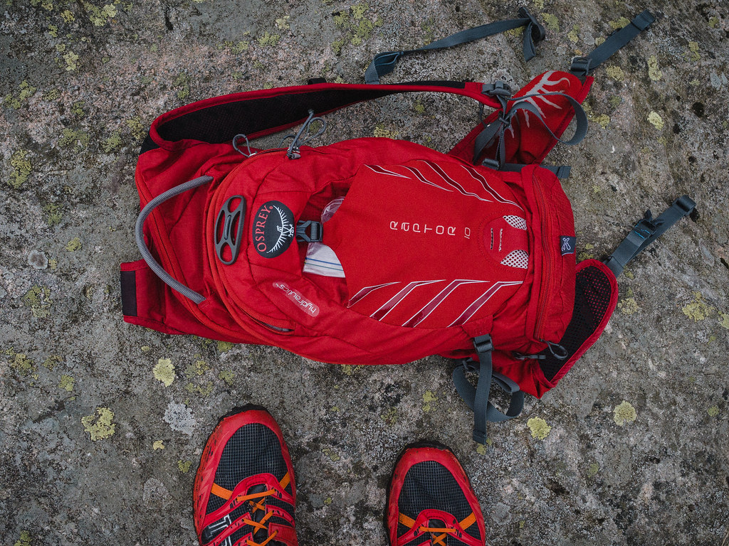 Red backpack and running shoes on rock.